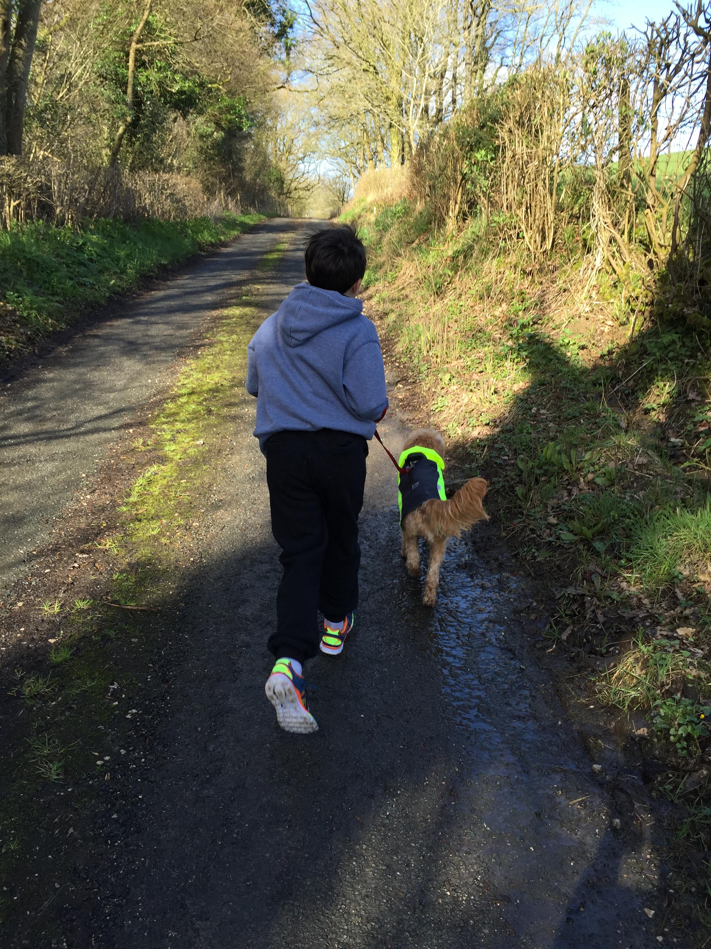 Boy running uphill with dog