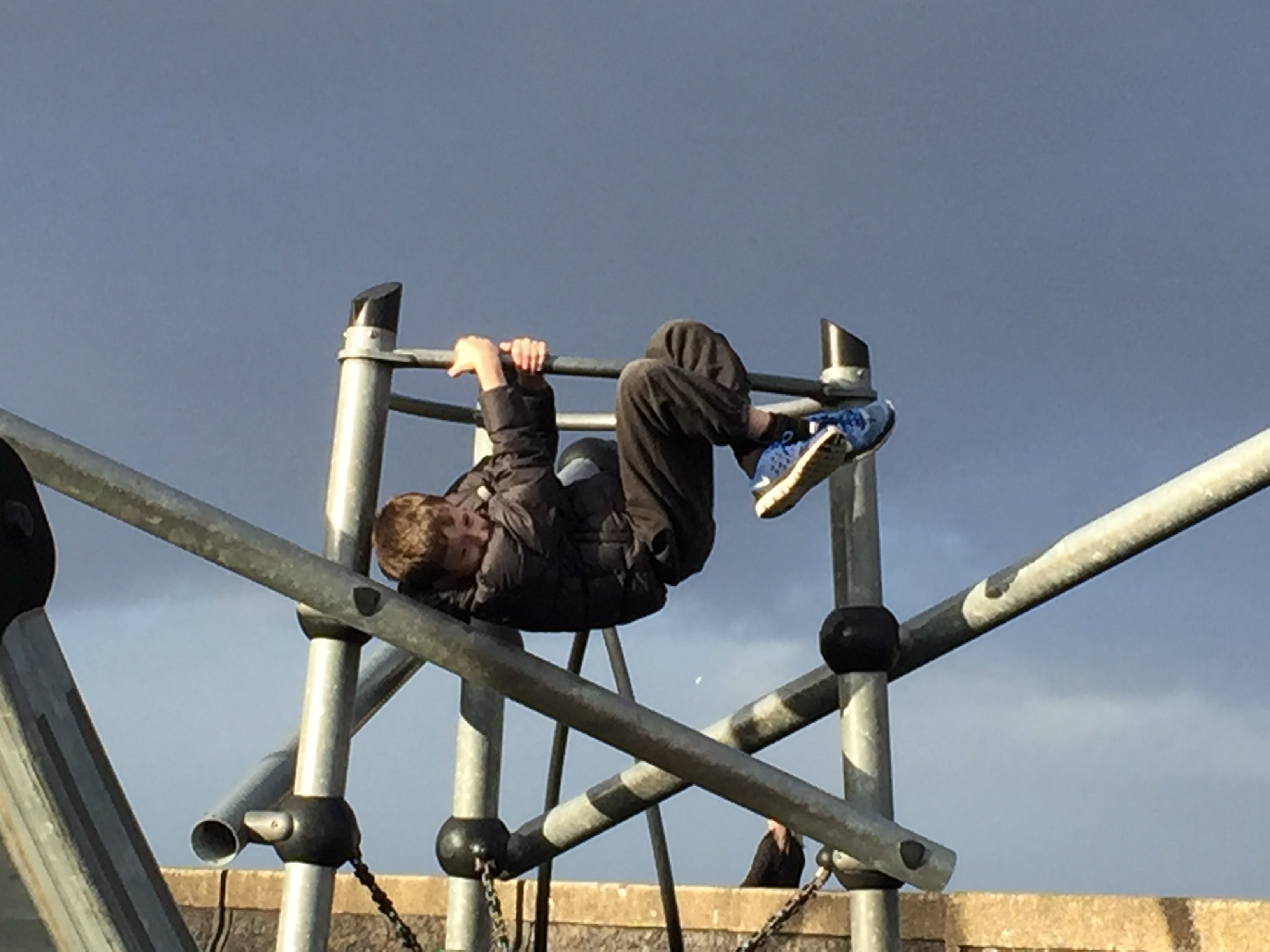 boy hanging from climbing frame