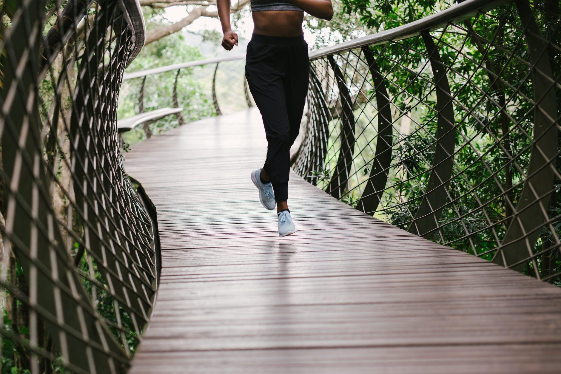 photo of person running on bridge